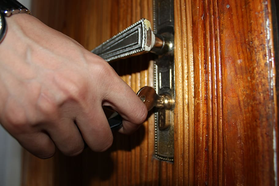 A guy using a key to open a door